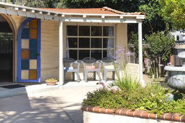 Sit and relax in the shade while the kids play outside in this open patio area.