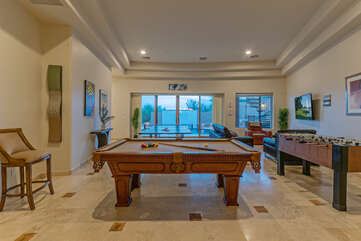 Game room on main level overlooks the custom pool with enchanting water wall.