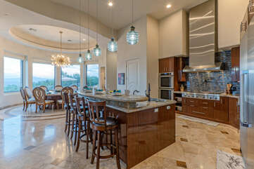 Kitchen has island seating and opens into a formal dining area with table seating and breathtaking golf and mountain views.