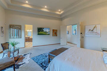 Similar to this primary suite on the main level, ALL bedrooms have king beds, TVs and ceiling fans.
