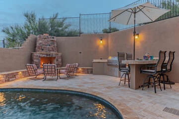 Tucked behind the pool on the main level balcony is a built-in gas fireplace and grill with bar seating.