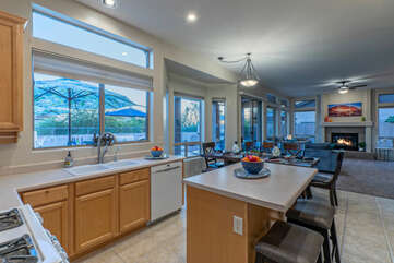 Completely stocked kitchen is open and bright with both table and island seating.