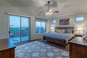 The lovely primary suite on the second floor features a king bed, TV, ceiling fan and private balcony.