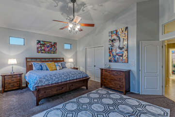 Classy primary suite has a king bed, TV, ceiling fan, private balcony and ensuite bath.
