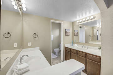 The private, en suite bathroom features a tile shower and his and her vanity sinks.
