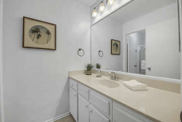 The hallway bathroom is located on the second floor next to Master Suite 1 and features a bathtub and shower combo and a vanity sink.