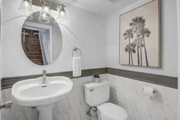 The powder room is located on the first floor next to the garage entrance and features a Pedestal sink.