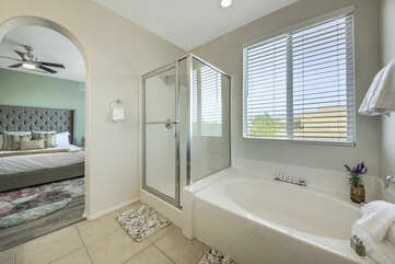 The private, en suite bathroom features a soaking tub, tile shower, and his and her vanity sinks and a makeup counter.