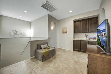 The upstairs landing area features a sitting area with a Smart TV.