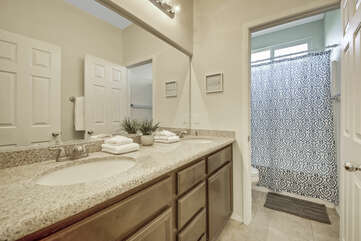 The upstairs hallway bathroom is located upstairs next to Bedroom 3 and features a soaking tub, tile shower and a vanity sink.