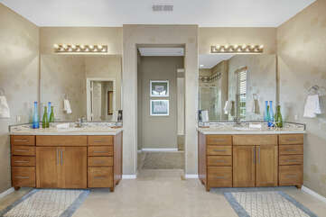 The private, en suite bathroom features his and her vanity sinks.