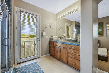 The en suite bathroom features a tile shower, and a vanity sink.