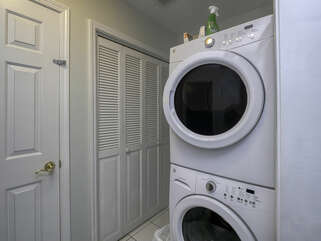 The laundry area with stacked full size washer and dryer