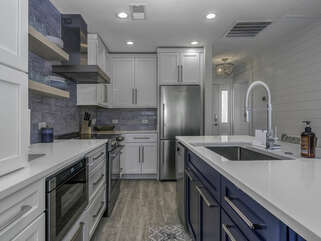 The beautiful renovated kitchen with white cabinets is a perfect spot for meal preparation.