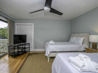 The first floor guest bedroom is spacious and bright with 2 queen beds and overhead ceiling fan